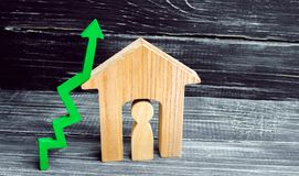 Wooden house with a man inside. green arrow up. concept of high demand for real estate. increase energy efficiency of housing. ris. E in house prices. property stock photo