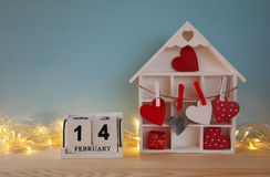Wooden house with many hearts and calendar Stock Photos