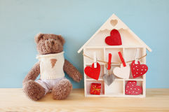 Wooden house with many hearts and cute teddy bear Stock Photo
