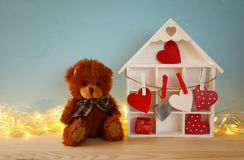 Wooden house with many hearts and cute teddy bear Royalty Free Stock Images