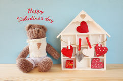 Wooden house with many hearts and cute teddy bear Royalty Free Stock Photo