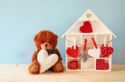 Wooden house with many hearts and cute teddy bear Royalty Free Stock Photography