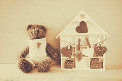 Wooden house with many hearts and cute teddy bear Stock Image