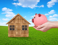 Wooden house on meadow and hand holding a pink piggy bank. Royalty Free Stock Images