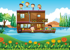 A wooden house in the middle of the river with kids Royalty Free Stock Photography