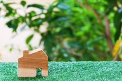 Wooden house model on artificial green grass. Property investment and house mortgage concept. Copy space stock images