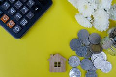Wooden house model, calculator and coins on light yellow background. Property investment, Home finance concept. Copy space for text stock photo