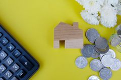 Wooden house model, calculator and coins on light yellow background. Property investment, Home finance concept. Copy space for text royalty free stock photos