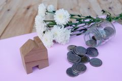 Wooden house model and coin flowing out from glass jar, all on wooden background. House finance, property investment concept. Wooden house model and coin flowing royalty free stock photo