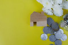 Wooden house model and coins on light yellow background. Property investment, Home finance concept. Copy space for text. Wooden house model and coins on light royalty free stock image