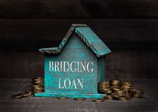 Wooden house model with coins next to it and hand. Wooden house model with coins next to it with conceptual text. Bridging loan Royalty Free Stock Images