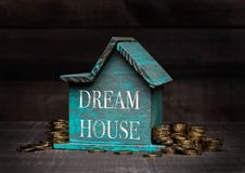 Wooden house model with coins next to it and hand Royalty Free Stock Photos