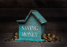 Wooden house model with coins next to it and hand Royalty Free Stock Images