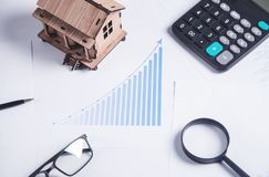 Wooden house model with financial chart. stock photography
