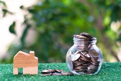 Wooden house model and glass jar with coins inside. Home mortgage and property investment concept. Copy space. Insurance door real-estate agent capital key royalty free stock images