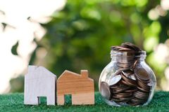 Wooden house model and glass jar with coins inside. Home mortgage and property investment concept. Copy space royalty free stock image