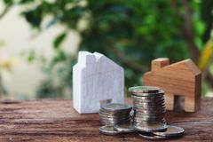 Wooden house model and pile of coins. Money for housing concept. Copy space stock photos
