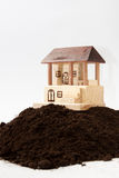 Wooden house model on the pile of soil Royalty Free Stock Photography