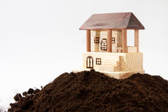 Wooden house model on the pile of soil Stock Photos