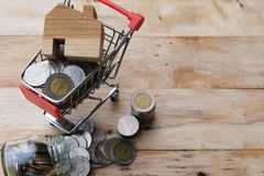 Wooden house model on shopping cart with coins flowing out from the glass jar. Buying house, house mortgage, property investment royalty free stock image