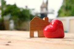 Wooden house model stand aside of big red heart. Happy home and family concept. Love concept. Wooden house model stand aside of big red heart. Happy home and royalty free stock photos