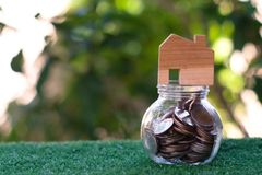 Wooden house model on top of glass jar which full of coins. Home mortgage and property investment concept. Copy space stock images