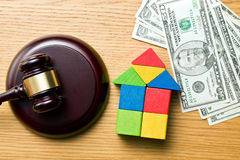 Wooden house with money and judge gavel Royalty Free Stock Image