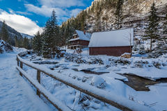 Wooden house at mountain river in winter, Tatra Mountains Stock Photo