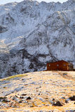 A wooden house in the mountains. Covered with first snow Stock Photos