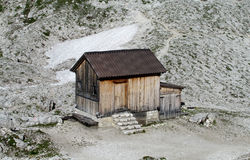 Wooden house in the mountains. House made of wood logs standing in the green alpine mountain foot path to the house. Gray rocks around. Hiking, trekking Stock Photo