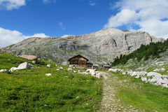 Wooden house in the mountains. House made of wood logs standing in the green alpine mountain forest, rocky mountain, green meadow and foot path to the house Stock Photography