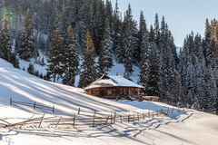 Wooden house in a nature area covered with freshly fallen snow. Royalty Free Stock Photography