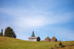 Wooden house near big reaps on sky background. Wooden house near big reaps on blue sky background stock photography