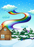 A wooden house near the pine trees with a rainbow uphigh Royalty Free Stock Image