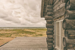Wooden house near the sea. Log house of log houses with a window and a terrace on the shores of the Baltic Sea with clouds Stock Photos