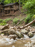 Wooden house near small waterfall Stock Photo