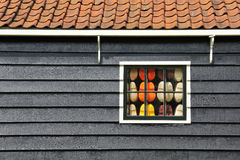 The wooden house of Netherlands and a window full of clogs inside. Stock Photos