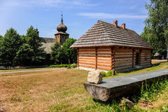 Wooden house next to the antique regional church in historic Polish village, Lesser Poland region, Poland Stock Photo