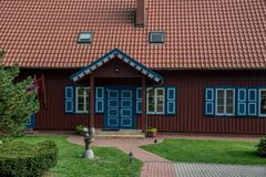 Wooden dark red house with blue windows and doors. Wooden house nicely decorated, Nida, Lithuania stock image