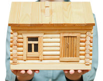 Wooden house on palms Stock Photos