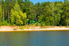 Wooden house peeks out of the pine forest on the Bank a river hot Sunny day. Wooden house peeks out of the pine forest on the Bank of a river on a hot Sunny day Stock Photography