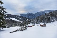 Wooden house in a perfect snowy winter landscape. Snow covered rural and forest landscape. royalty free stock photo