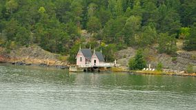 Wooden house and pier on green coast of island of Turku archipelago stock photo
