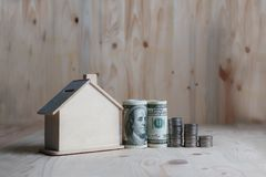 Wooden house piggy bank with dollar money and coin on wooden table over wood background metaphor saving money for buy home and. Real estate stock photo
