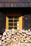 Wooden house with pile of wood logs ready for winter Stock Photos
