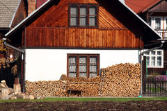 Wooden house with pile of wood logs ready for winter Royalty Free Stock Images