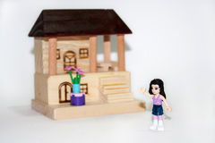 Wooden house and plastic toys Royalty Free Stock Image