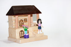 Wooden house and plastic toys Stock Photography