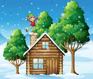 A wooden house with a playful elf at the rooftop Royalty Free Stock Photos