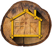 Wooden House Project Concept. Wooden meter ruler in the shape of house in a section of tree trunk isolated on white background royalty free illustration